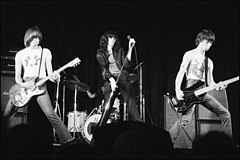 A black and white picture of a rock band with four members shown performing on stage.