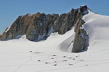 mountain hut on rock outcrop with climbers camping on nearby glacier