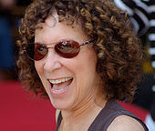 Smiling young woman with short, curly brown hair and sunglasses