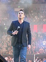 A middle-aged, brown-haired man wearing a jacket and jeans walks on what appears to be a stage, holding a microphone to his chest and looking upward. An audience is in the background.