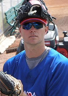 A pale-skinned man wearing a blue baseball pullover and blue reflective sunglasses with a baseball glove atop his head