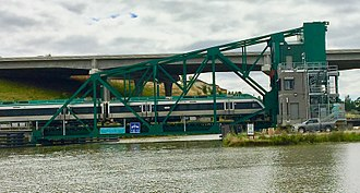 Sonoma–Marin Area Rail Transit - A northbound SMART train crosses the Petaluma River on a drawbridge previously used on the Galveston Causeway in Texas. Note US 101 on the taller bridge in the background.