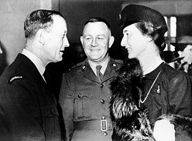 Two uniformed men with a woman in a dark dress, hat and fur stole