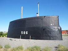 A very large submarine conning tower in a gravel park.