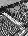 Sailors unload shells from a barge at Sasebo in 1950.jpg