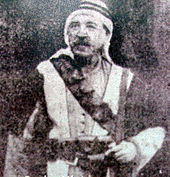 Grainy photo of mustachioed man in traditional dress