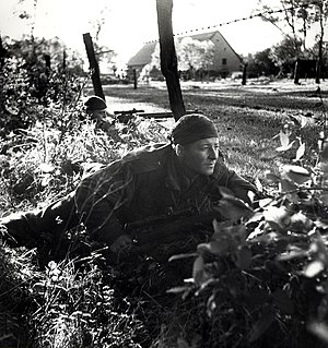 Battle of the Scheldt - Corporal Kormendy, a scout from the Calgary Highlanders Scout and Sniper Platoon, in a shot from a series of staged photos by Army photographer Ken Bell, taken near Kapellen, October 1944