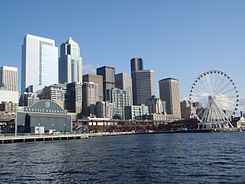 Vew of the downtown Seattle skyline, on the waterfront, with the Seatle Aquarium on the left and Seattle Great Wheel on the right.