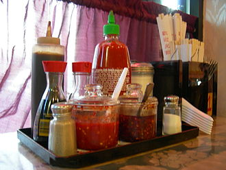 Pho - Tables at pho restaurants abroad are set with a variety of condiments,  including Sriracha sauce, and eating utensils.