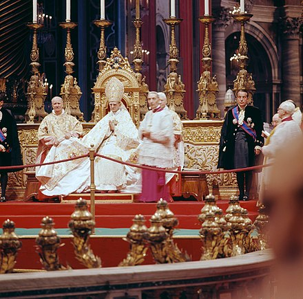 Saint Pope Paul VI presiding over the introductory ingress of the Council, flanked by Cardinal Alfredo Ottaviani (left), Cardinal Camerlengo Benedetto Aloisi Masella and Monsignor Enrico Dante (future Cardinal), Papal Master of Ceremonies (right), and two Papal gentlemen. Second Vatican Council by Lothar Wolleh 001.jpg