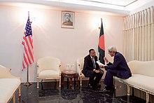 AH Махмуд Али и Джон Керри, сидя близко друг к другу и говорить