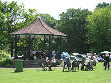 Grassy area with people sitting in chairs in front of a bandstand with tiled roof.