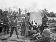 Rear view of an artillery gun mounted on a wheeled carriage. Palm trees, damaged buildings and smoke are visible in front of the gun's barrel. Three shirtless men are working on the gun while another three shirtless men are standing in a line to its left each holding a single artillery shell.