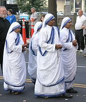 Four nuns up in sandals n' white-and-blue saris