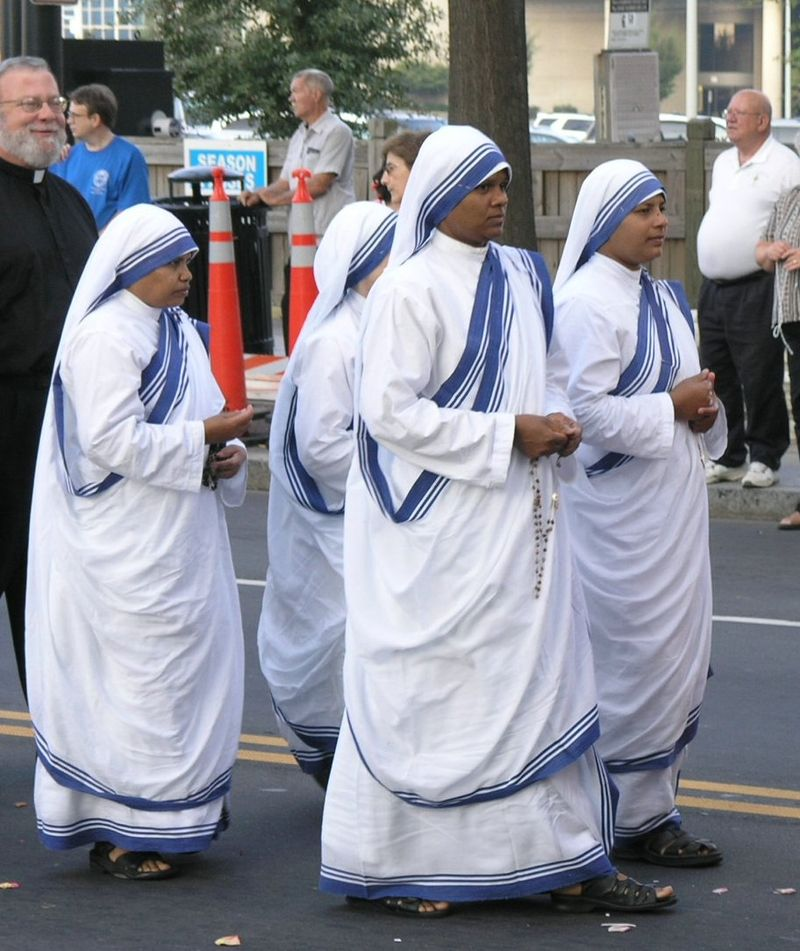 Four nuns in sandals and white-and-blue saris