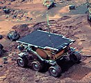 A Mars rover, topped with solar panels, on reddish-brown terrain.