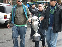 Two men carry a bright silver trophy with another man walking behind holding a green and blue scarf overhead.