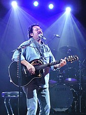 A man with dark hair and mustache playing guitar and singing into a microphone