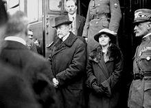 Серьезный Масарик с дочерью выходят из поезда в окружении людей.