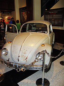 A light tan rusty Volkswagen is positioned for display behind a chain made of handcuffs