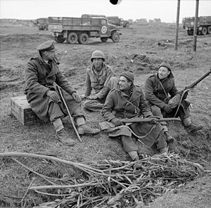 169th (3rd London) Brigade - Reverend G B Fairhurst, Padre of the 2/5th Battalion, Queen's Royal Regiment, talking to two of the men in his battalion and an American soldier in the Anzio bridgehead, Italy, 20–21 February 1944.
