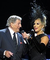 A man and a woman standing closely together. The man (left) is wearing a grey suit, white shirt and a black tie while the woman (right) is wearing a black gown, black gloves and a black headpiece. They both hold a microphone in their left hand.