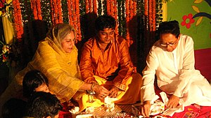 English: Relatives decorating the groom with t...
