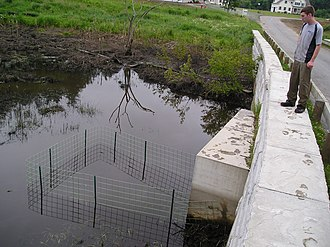 Flow device - Trapezoidal protective fence installed after re-opening dammed culvert