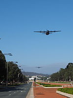 Two C-130 Hercules transport aircraft flying up Anzac Parade