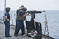 U.S. Navy Gunner's Mate 2nd Class Raymond Oliveros, foreground right, fires an M240 machine gun aboard the guided missile destroyer USS Preble (DDG 88) in the Pacific Ocean during a live-fire weapons shoot 130619-N-TX154-335.jpg