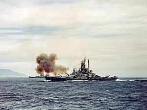 Color photo of a warship at sea. Smoke is rising from the bow of the ship, and land is visible in the background.