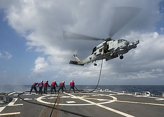 Raising a hose from USS Mustin to an MH-60R Sea Hawk