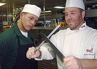 US Navy 031204-N-1711I-001 Mess Management Specialist 3rd Class Benjamin AlmodovarPacheco from Ceiba, Puerto Rico, watches carefully as culinary arts instructor Chef Sam Glass trains him on the best way to sharpen a butcher's.jpg