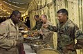 US Navy 051124-F-9927R-001 U.S. Navy Rear Adm. Mike Lefever, center, serves Thanksgiving Dinner along side 212th Mobile Army Surgical Hospital (MASH) Commander Col. Lugo and Command Sgt. Maj. Ramdass.jpg
