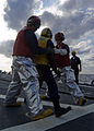 US Navy 080218-N-5253W-007 Damage Controlman 3rd Class Clifford Valasco and Gunner's Mate 3rd Class Joseph Frenz transport a victim from a simulated helicopter crash on the flight deck of the Arleigh Burke-class guided-missile.jpg