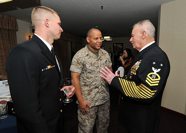"Two senior enlisted servicemembers chat with BMCM (SEAL) (Ret.) Rudy Boesch during a 2010 ""Dining Out"" event commemorating the 117th birthday of the chief petty officer corps. His dress blue uniform has gained note for how many ribbons, medals, and stripes it bears. US Navy 100401-N-2013O-001 Chief Explosive Ordnance Disposal Technician Daniel Martin, from Houston, and Gunnery Sgt. Tony Smith, from Columbus, Ohio, chat with Master Chief Boatswain's Mate (SEAL) (Ret.) Rudy Boesch during a C.jpg"