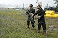 US Navy 100723-N-1906L-006 Master-at-Arms 3rd Class Anthony Lebya, left, and Master-at-Arms 3rd Class Jesse Van Winkle handle concertina wire to create a protective perimeter.jpg