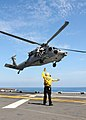US Navy 110812-N-YG354-026 Aviation Boatswains Mate (Handling) 2nd Class Patrick Morrison directs a MH-60S Sea Hawk helicopter.jpg
