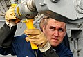 US Navy 111117-N-FH966-482 Fire Controlman 2nd Class Jacob Barnes uses a drill to drive a Sea Sparrow missile into the launcher.jpg