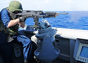 US Navy 111212-N-ZF681-897 Gunner's Mate 2nd Class Erik Trudel fires a M-240 machine gun aboard the guided-missile destroyer USS Halsey (DDG 97).jpg