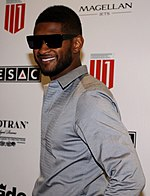 A man is wearing sunglasses and is facing smiling towards the camera.