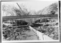 VIEW OF SOUTH (DOWNSTREAM) ELEVATION - Oconaluftee Bridge, Spanning Oconaluftee River, Cherokee, Swain County, NC HAER NC,87-CHER,1-1.tif