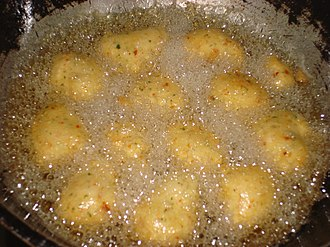 Vada (food) - Medu vada being deep-fried in oil