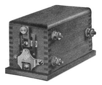 """Trembler coil - A trembler coil, around 1915.  The mechanism on the end is the """"trembler""""."""