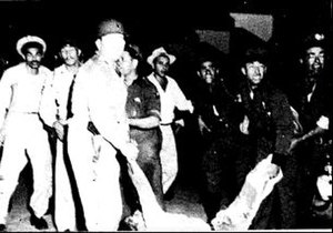 San Juan Nationalist revolt - A wounded Vidal Santiago Díaz is carried out of his barbershop by the police