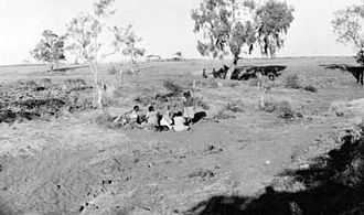 Wave Hill Station - Group of Aboriginal women and children sitting in gully at Wave Hill, 1924