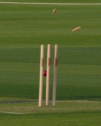 English: Wicket, the stumps being hit by a ball