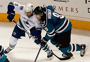 Willie Mitchell (ice hockey) -  alt = An ice hockey player dressed in a white and blue jersey attempting to impede another player dressed in a teal and black jersey with his stick.