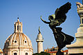 Winged Victory (Nike) bronze statue against background of Trajan's Column and dome of Santa Maria di Loreto church. Rome, Italy.jpg