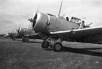 Row of single-engined military monoplanes on airfield, propellers spinning